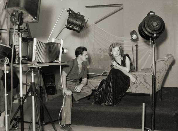"Typical studio set up, with the large ""hot lights"" and cumbersome sheet film camera."